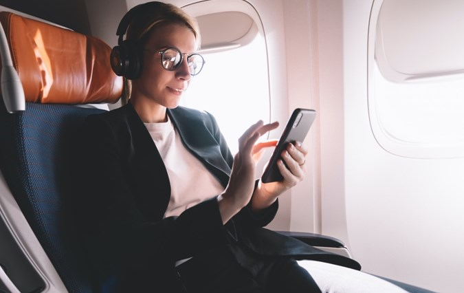 Woman in airplane holding her phone